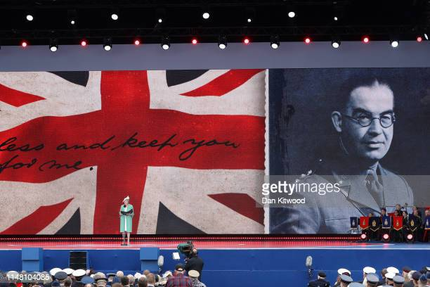 British Prime Minister, Theresa May reads a letter written by Captain Norman Skinner of the Royal Army Service Corps on stage during the D-Day...
