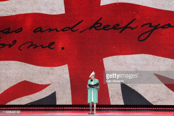 British Prime Minister Theresa May reads a letter written by Captain Norman Skinner of the Royal Army Service Corps on stage during the DDay...