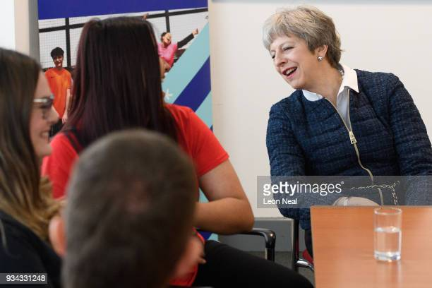 British Prime Minister Theresa May reads a tshirt logo as she talks with young people at the 'Street League at People Plus' employment charity on...