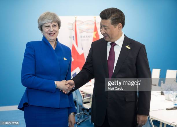 British Prime Minister Theresa May shakes Chinese President Xi Jinping hand as they hold a bilateral meeting during the G20 summit on July 7 2017 in...