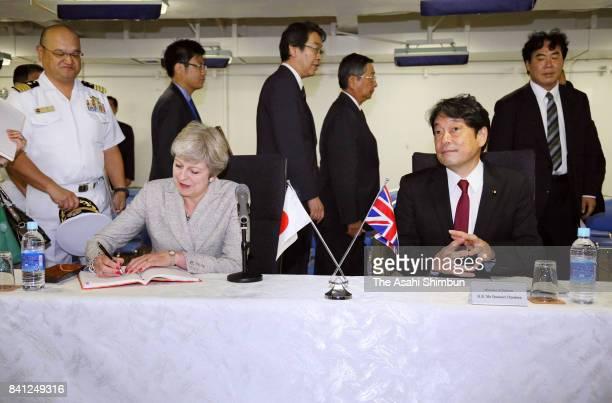 British Prime Minister Theresa May signs a visitors book while Japanese Defense Minister Itsunori Onodera watches at Japan Maritime SelfDefense Force...