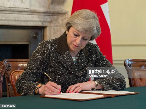 British Prime Minister Theresa May signs the official letter to European Council President Donald Tusk invoking Article 50 and the United Kingdom's...