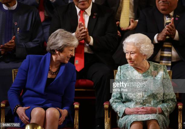 British Prime Minister Theresa May sits with Queen Elizabeth II attend the formal opening of the Commonwealth Heads of Government Meeting in the...