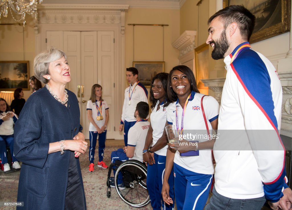 British Prime Minister Theresa May speaks to Asha Philip, Perri Shakes-Drayton and Martyn Rooney during a reception for who competed in the World Athletics Championships and World Para Athletics at 10 Downing Street on August 22, 2017 in London, England.