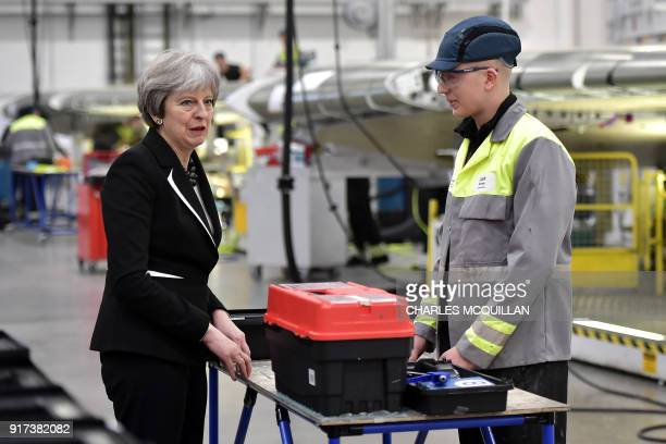 British Prime Minister Theresa May speaks to Josh Barnes an operations worker during a visit to the Belfast Bombardier factory in Belfast on February...