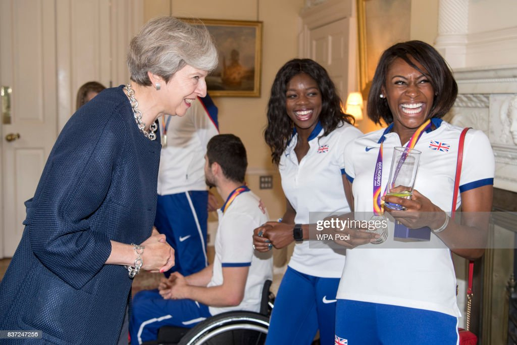 British Prime Minister Theresa May speaks to Perri Shakes-Drayton (R) and Asha Philip a reception for who competed in the World Athletics Championships and World Para Athletics at 10 Downing Street on August 22, 2017 in London, England.