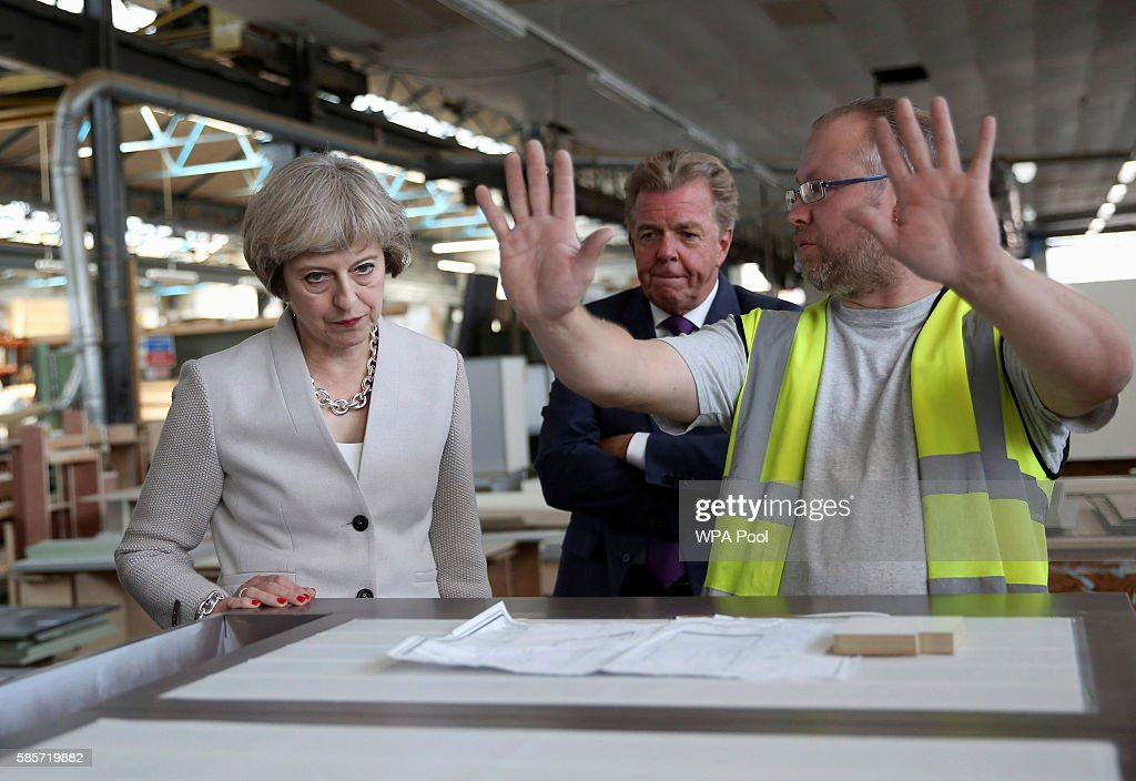 British Prime Minister Theresa May speaks with a worker as Martek Managing Director Derek Galloway looks on during a to joinery factory on August 3, 2016 in London, United Kingdom.
