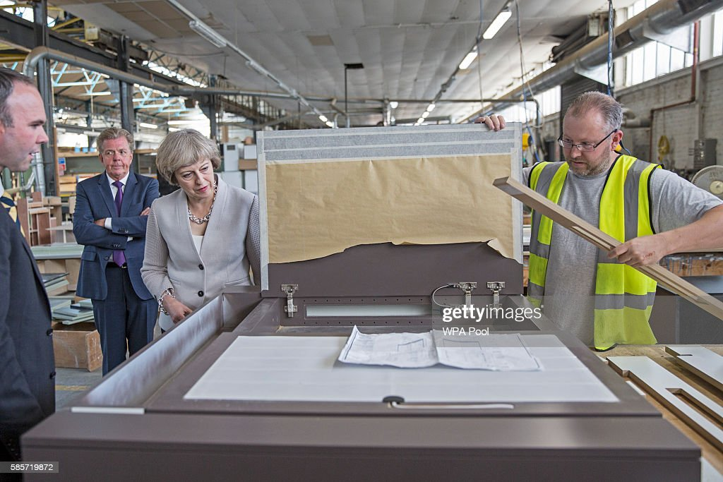 British Prime Minister Theresa May speaks with a worker as she visits Martinek joinery factory on August 3, 2016 in London, United Kingdom.