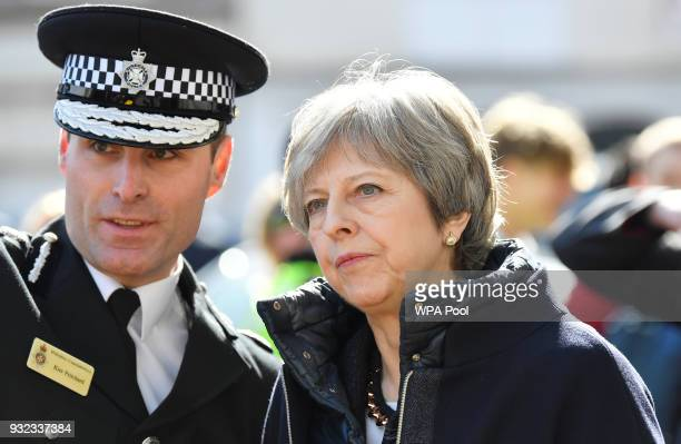 British Prime Minister Theresa May speaks with an officer as she visits the city where former Russian intelligence officer Sergei Skripal and his...