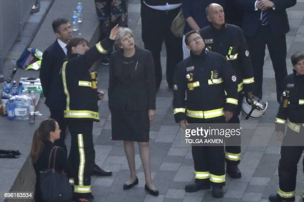 TOPSHOT British Prime Minister Theresa May speaks with Dany Cotton London Fire Brigade commissioner as she visits the remains of Grenfell Tower a...