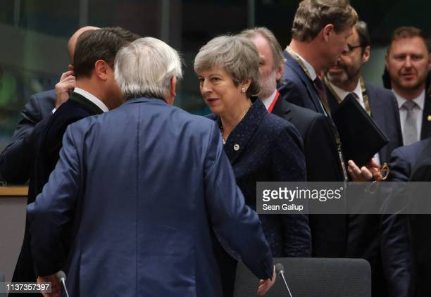 British Prime Minister Theresa May speaks with European Commission President JeanClaude Juncker as she arrives for the roundtable session on the...