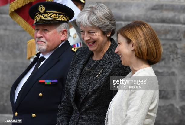 British Prime Minister Theresa May speaks with French Defence Minister Florence Parly in Amiens northern France on August 8 to attend a ceremony to...