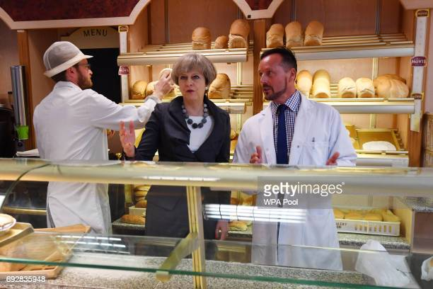 British Prime Minister Theresa May stands behind the counter inside a bakery during an election campaign visit on June 6 2017 in Fleetwood northwest...