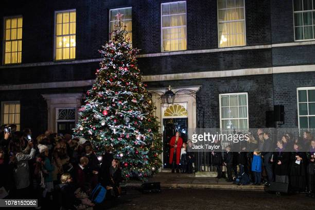 British Prime Minister Theresa May switches on the Christmas tree lights outside Number 10 Downing Street with three school children on December 06...