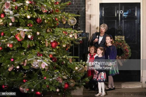 British Prime Minister Theresa May switches on the Christmas tree lights with Emily Wood Lily Bo Morgan and Sophie Vysata who designed the Prime...