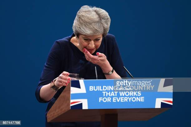 British Prime Minister Theresa May takes a cough sweet as she struggles with a cough during her keynote speech to delegates and party members on the...