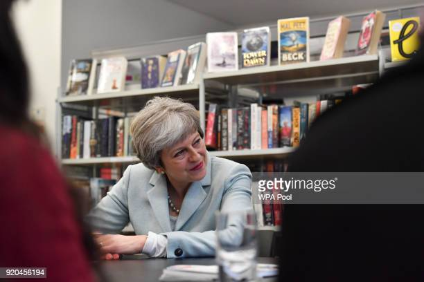 British Prime Minister Theresa May talks with pupils and staff during her visit to Featherstone High School in Southall on February 19 2018 in London...