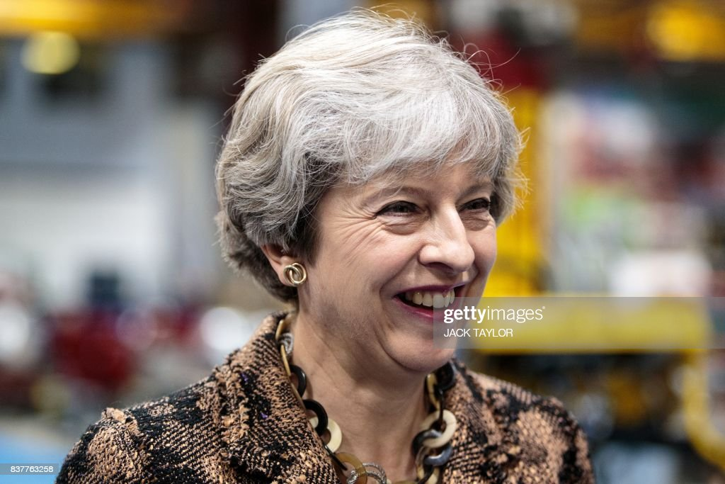 British Prime Minister Theresa May talks with workers as she tours the Alexander Dennis bus and coach manufacturers factory in Guildford, south of London, on August 23, 2017. The company has secured a 44-million GBP government finance deal to sell Britain's famous red double-decker buses to Mexico. A £1.7 billion package of taxpayer-funded support to help businesses make the most of opportunities outside of the European Union has helped 137 firms expand and win overseas contracts over the past year, the prime minister said. / AFP PHOTO / POOL / Jack Taylor