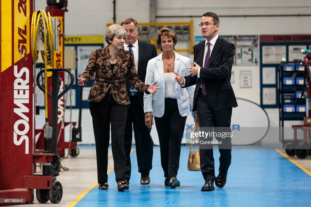 British Prime Minister Theresa May (L) tours the Alexander Dennis bus and coach manufacturers factory in Guildford, south of London, on August 23, 2017. The company has secured a 44-million GBP government finance deal to sell Britain's famous red double-decker buses to Mexico. A £1.7 billion package of taxpayer-funded support to help businesses make the most of opportunities outside of the European Union has helped 137 firms expand and win overseas contracts over the past year, the prime minister said. / AFP PHOTO / POOL / Jack Taylor