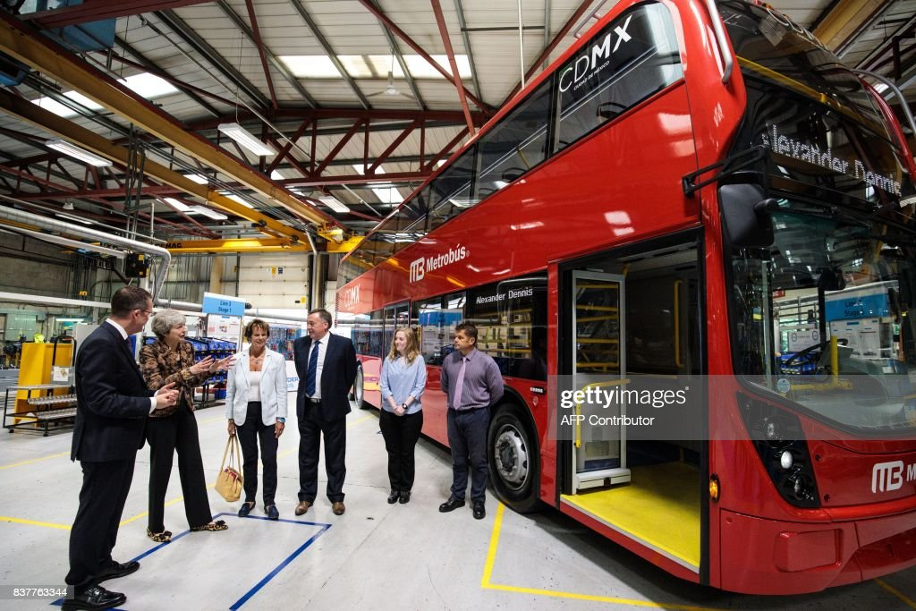 British Prime Minister Theresa May (2L) tours the Alexander Dennis bus and coach manufacturers factory in Guildford, south of London, on August 23, 2017. The company has secured a 44-million GBP government finance deal to sell Britain's famous red double-decker buses to Mexico. A £1.7 billion package of taxpayer-funded support to help businesses make the most of opportunities outside of the European Union has helped 137 firms expand and win overseas contracts over the past year, the prime minister said. / AFP PHOTO / POOL / Jack Taylor