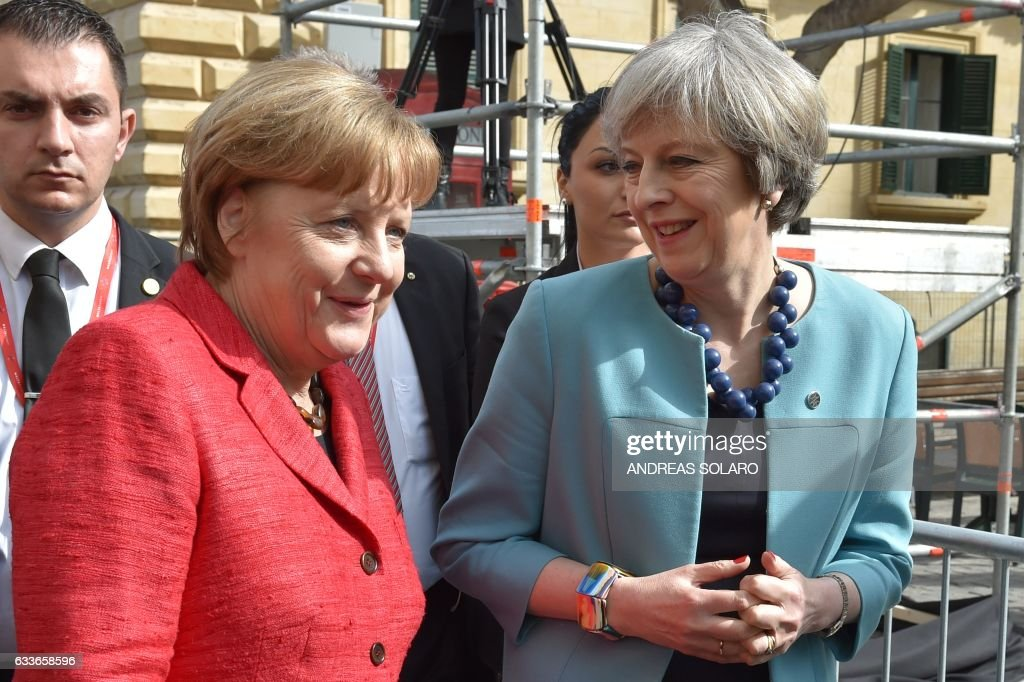 British Prime Minister Theresa May (R) walks along with Germany's Chancellor Angela Merkel (L) before a family picture during an European Union summit on February 3, 2017 in Valletta, Malta. European Union leaders will try to rally together to revive the beleaguered bloc at a special summit in Malta Friday in the face of 'threats' from migration, Brexit and Donald Trump. It is the latest in a series of crisis meetings since Britain voted to leave the EU last June, but fears about the new US president have strengthened the sense that the bloc is now at a decisive moment in its history. / AFP / Andreas SOLARO