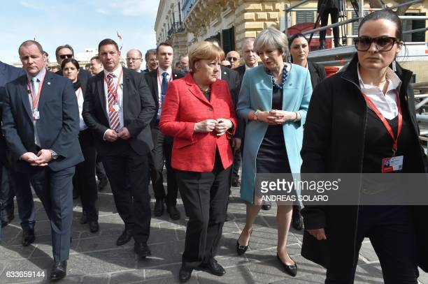 British Prime Minister Theresa May walks along with Germany's Chancellor Angela Merkel surrounded by bodyguards before a family picture during an...