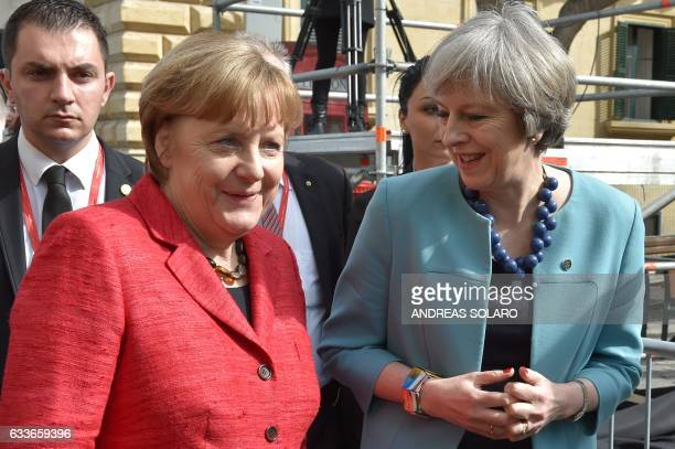 British Prime Minister Theresa May walks along with Germany's Chancellor Angela Merkel before a family picture during an European Union summit on...
