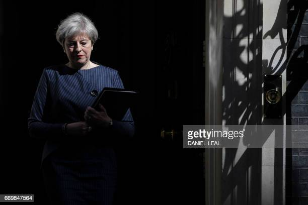 British Prime Minister Theresa May walks out of 10 Downing Street to speak to media in central London on April 18 2017 British Prime Minister Theresa...