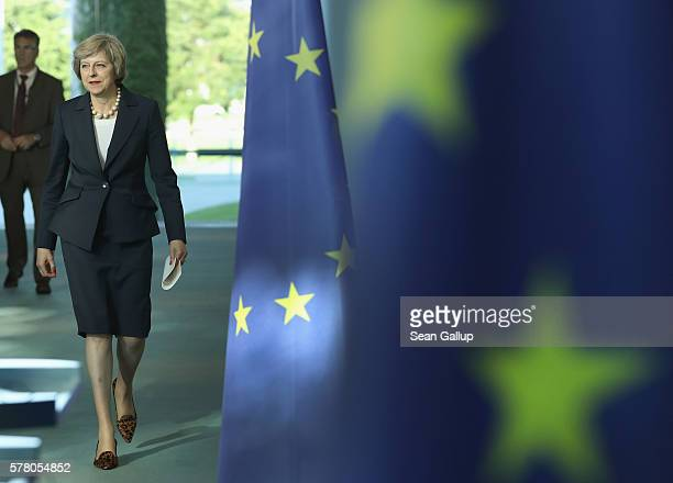 British Prime Minister Theresa May walks past European Union flags as she and German Chancellor Angela Merkel arrive to speak to the media following...