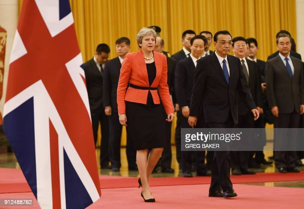 British Prime Minister Theresa May walks with Chinese Premier Li Keqiang during a welcome ceremony in the Great Hall of the People in Beijing on...