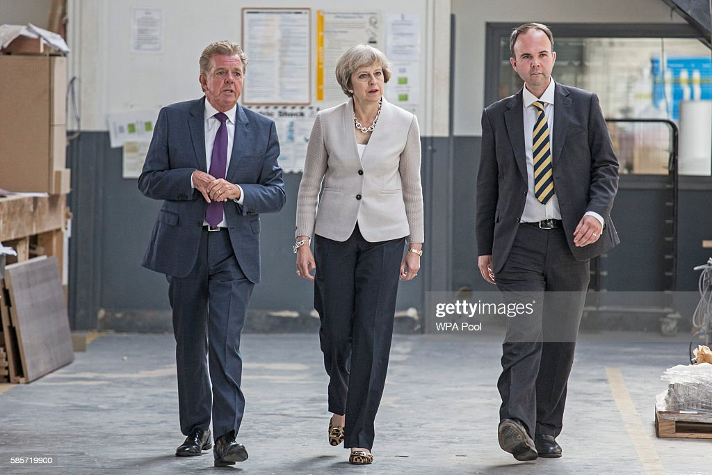 British Prime Minister Theresa May walks with Martek Managing Director Derek Galloway and Croydon Central MP Gavin Barwell (R) during a visit to Martinek joinery factory on August 3, 2016 in London, United Kingdom.