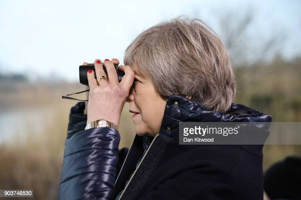 British Prime Minister Theresa May watches birds from inside a bird hide with school children at the London Wetland Centre on January 11 2018 in...