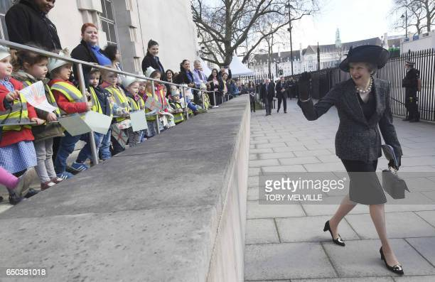 British Prime Minister Theresa May waves to a crowd of children as she leaves after attending the unveiling of The Iraq and Afghanistan memorial at...