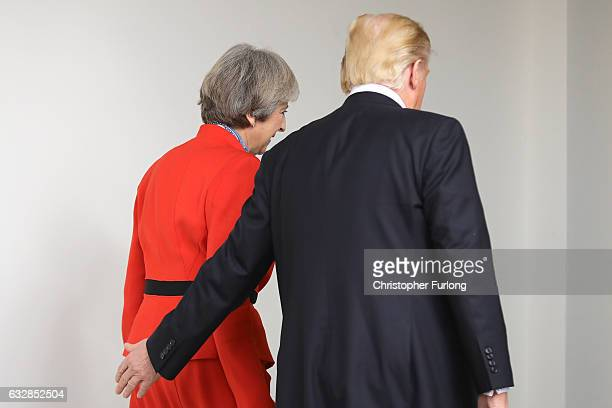 British Prime Minister Theresa May with US President Donald Trump as they walk along The Colonnade at The White House on January 27 2017 in...
