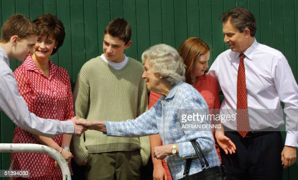 British Prime Minister Tony Blair and his son Euan wife Cherie Nicholas and daughter Kathryn meet a local woman outside the polling station in...