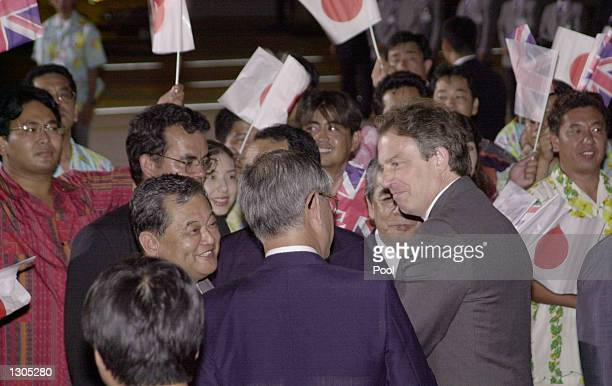 British Prime Minister Tony Blair, profile right, is escorted upon arrival at Naha Airport by the Governor of Okinawa, Keiichi Inamine, center back...