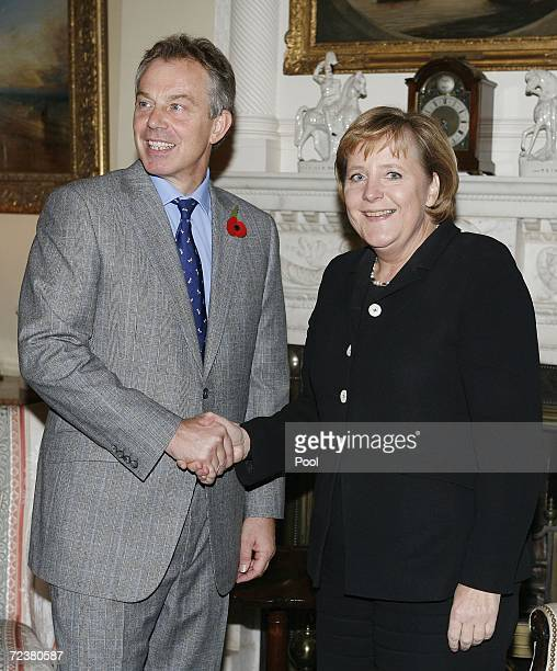 British Prime Minister Tony Blair right shakes hands with the German Chancellor Angela Merkel on her arrival at Blair's London residence 10 Downing...