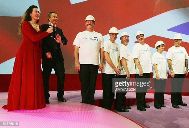 British Prime Minister Tony Blair shyly accepts to sing along with Welsh opera singer Susanne Clark and a male choir 30 September 2004 at the...