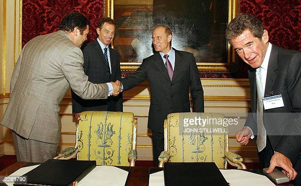 British Prime Minister Tony Blair stands aside as President Valadimir Putin of Russia shakes hands 26 June 2003 with Mikhail Fridman Chairman of the...
