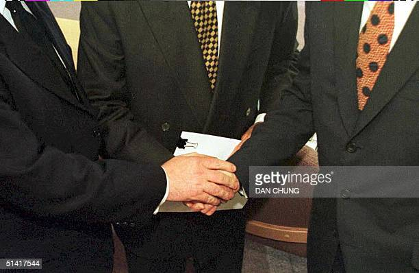 British Prime Minister Tony Blair US Senator George Mitchell and Irish Prime Minister Bertie Ahern shake hands after they signed the historic...