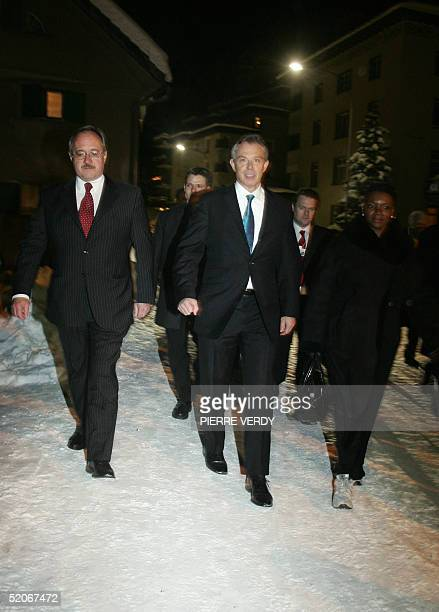 British Prime Minister Tony Blair walks flanked by Swiss President Samuel Schmidt on his way to reach the World Economic Forum congress hall to...