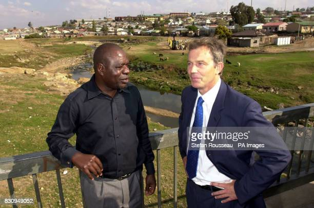 British Prime Minister Tony Blair with Mbazima Shilowa President of Gauteng Province in the Township of Alexandra near Johannesburg where he saw a...