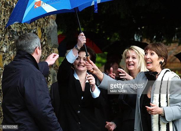 British Prime minister Tony Blair's wife Cherie fights with her umbrella helped by actress Anita Harris before entering the church of St Mary The...