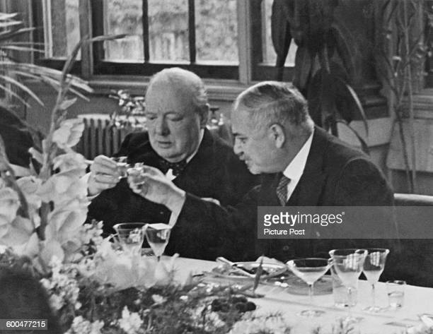British Prime Minister Winston Churchill clinks glasses with Soviet Ambassador Ivan Maisky at a lunch party given by the ambassador for...