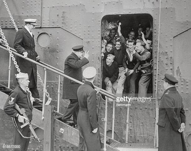 British Prime Minister Winston Churchill giver the victory sign as he receives the good wishes of the sailors and Airmen upon disembarking from the...
