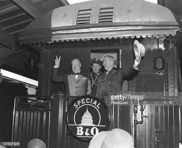 British Prime Minister Winston Churchill gives a 'V for Victory' sign as he and US President Harry S Truman wave from the back of the President's...