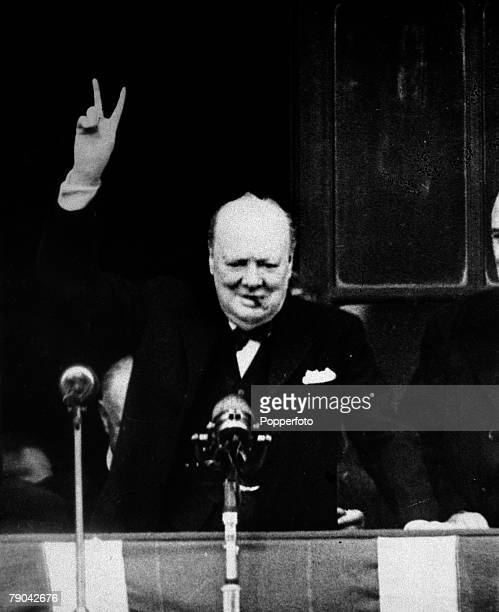 British Prime Minister Winston Churchill gives his famous victory sign after a short speech from the balcony of the Ministry of Health building to a...