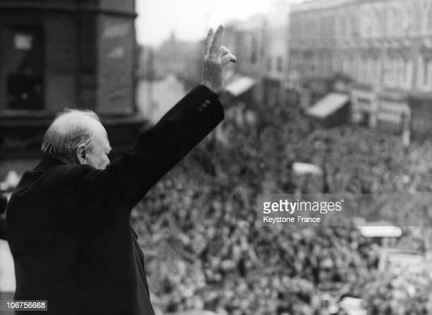British Prime Minister Winston Churchill gives his famous victory sign from the balcony of the Ministry of Health building to a huge crowd below as...
