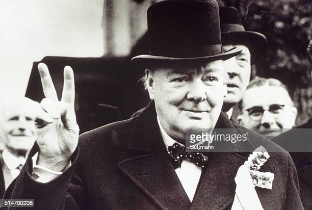 British Prime Minister Winston Churchill gives the victory sign to onlookers.