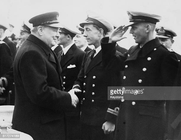 British Prime Minister Winston Churchill greets officers of the British Royal Navy heavy cruiser, HMS Exeter, on their return from the Battle of the...